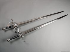 These two 16th century longswords have complex compound-hilts and are mounted onto twin-fullered blades of hexagonal cross-section. One blade is a typical Oakeshott Type XIX with the characteristic ricasso, the other was made without the ricasso.