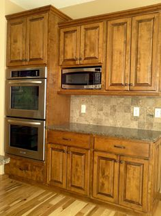 LDK home with double stack oven, wood cabinets, tile backsplash and granite countertops.