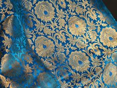 Brocade Fabric, indian brocade, Banaras silk, Silk Brocade Fabric. This is a beautiful pure heavy Banarasi silk brocade floral design fabric in Turquoise Blue and Gold. The fabric illustrate golden...