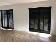 Zwarte kozijnen, witte muren, houten visgraat vloer