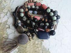 Wickelarmband 9 reih. geknotet mit einem schwarzen synt.Band und Halbedelsteinen (Jade Rosenquartz)und Glasperlen. Geschlossen wird das Armband mit einem schwarzen Lederband und einem Metall Knopf. Anhänger ist eine Rosenquartz Perle, eine Glasperle, eine Metall Blüte und eine Quaste aus Seide/Baumwolle/Synt..  Wickelarmband kann auch als Kette getragen werden.  Farbe dunkelgrau, rose, beige, rot, schwarz, silber  josefine1961 by DaWanda.com