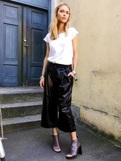 Pernille Teisbaek wears a white t-shirt, leather culottes, and mules