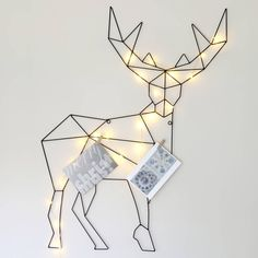 Reindeer Card Holder. Striking card holder wall decoration with copper wire light garland option. Show a lovely selection of Christmas cards with this metal reindeer card holder.