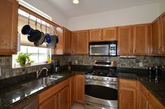 Traditional Kitchen with Canyon Creek Shaker Cabinetry, Stone Tile, Flat panel cabinets, Complex Granite, U-shaped
