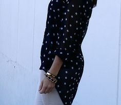 Polka dot top and gold and black jewelry.