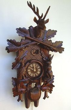 "Model #8T 285/9 Hunters Cuckoo Clock with Live Animals     Hunter's cuckoo clock with live animals (upright), 24"" Tall, German Regula 8 day movement (must be wound weekly), Hand-carved, Wooden dial,   Wooden hands,   Wooden cuckoo bird,   Night shut-off switch,   Antique stain,   Made by Anton Schneider,   2 Year warranty."