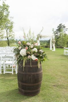 Spring wedding ceremony decor - wine barrel with lush flower arrangements at outdoor ceremony {Erica Akroyd Photography}