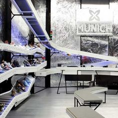 Shoes are displayed on conveyor belts at this store in Barcelona by Spanish firm Bailo+Rull ADD Arquitectura. Designed for shoe brandMunich, the interior has reflective walls while peep-holes in the facade allows shoppers to glimpse behind-the-scenes of the store. Photographs are by Albert Marín unless stated otherwise. Above image is by Pol Viladoms The following …