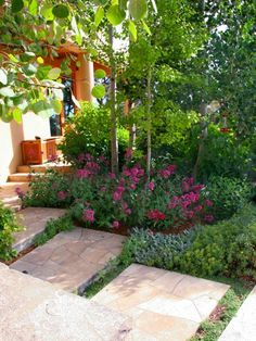 French limestone and concrete combine for a spacious path that ties together the public and private sides of the home. Freeform tumbles of plantings around and between the stones lend a casual feel.