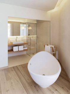 baño con lavabo sobre encimera de madera con estantería inferior, cabina de ducha con cerramiento de vidrio, bañera exenta y suelo parquet
