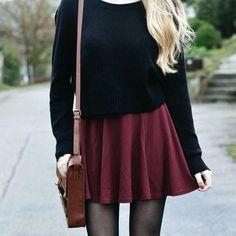 Jupe bordeaux évasée style patineuse, portée avec un pull noir et un sac en cuir…