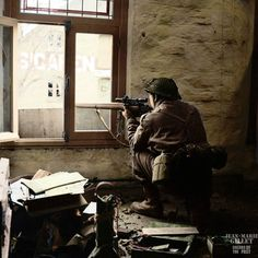 """A sniper from """"C"""" Company, 5th Battalion, The Black Watch, 51st (Highland) Division, takes aim through the window of a building in Gennep, Netherlands."""
