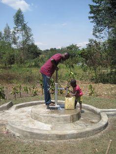 Mpigi, Uganda. Father & son at the water pump.
