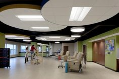 A colorful, cloud-like floating ceiling helps control acoustics in the group physical therapy room of The Joint Center, while providing appropriate lighting for patients and staff. The lower ceiling creates an intimate scale, bridging the space between the open ceiling and finishes in the rest of the environment. Photo: Aker Imaging, Houston.