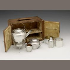 A six piece Victorian silver travelling picnic tea set, designed by Dr. Christopher Dresser, made by Heath & Middleton, retailed by Leuchar and Sons, London 1892, comprising: a kettle on stand, a tea pot, a cream jug, a sugar bowl, a tea caddy, the screw off base forming the spirit burner, wicker bound scroll handles, the pull off covers with ring handles, in a fitted velvet lined Leuchars travelling case, height of kettle on stand 23cm, weight 30oz. (6)