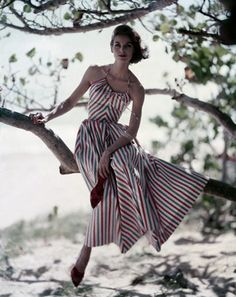 Famous Model Anne St.Marie is wearing a red, white and blue striped dress, with halter top and a full ankle-length skirt, with red stiletto mules, by Hope Skillman, 1957.