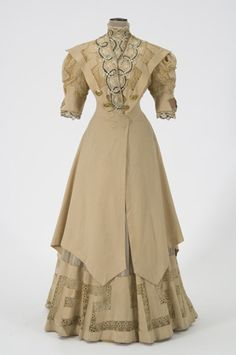 (View 2 with tunic) 1905 Woman's suit constructed of light yellowish brown wool and yellowish white silk chiffon is trimmed with lace of embroidered net underlaid with cloth of black and gold threads. Suit day bodice consists of a tunic length jacket open from waist with an uneven hemline and train.