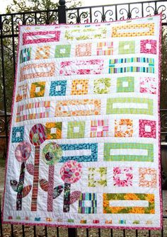 gorgeous jelly roll quilt pattern that uses geometric shapes and cute little flowers to make a really sensational design. Combine different jelly rolls and make a bright collage of color.