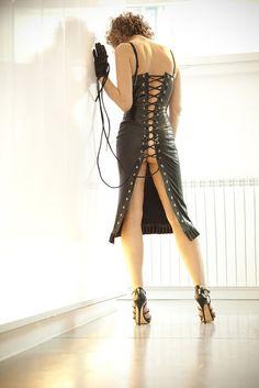 Mistress Fidelia di Milano in abito in latex con la sua frusta in mano e sta aspettando uno schiavo da sodomizzare e torturare.