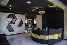 Entrance/Reception of a high-end salon, designed and built by Landscape PLC, featuring monochrome angular ceiling, gold finish reception desk and hexagon products' display wall. Stay tuned for more views! #landscapeplc #saloninterior #interiordesign #gold #finish #reception #displaywall