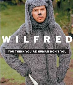 """""""Elijah Wood and Jason Gann star in the new show about a struggling and suicidal ex-lawyer named Ryan (Wood) who befriends his neighbor's dog Wilfred (Gann), even though he sees him as a man in a dogsuit. Fiona Gubelmann also stars as Ryan's attractive neighbor and Wilfred's owner, Dorian Brown as Ryan's controlling sister Kristen"""""""