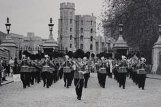 Drum Major Tom Cornall leading the Band of the Grenadier Guards out of the Main gate of Windsor Castle in the 1950s
