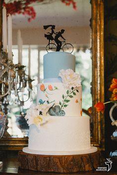 Bolo de casamento pintado à mão. No segundo andar, flores pintadas e flores de açúcar para decorar. Como topo de bolo, um casal pedalando juntos.