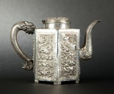 Hexagonal silver teapot with dragon handle and engraved and embossed decoration of battle scene in medallions