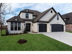 Painted white brick house with board and batten over garage, black trim, black soffit, black fascia, black garage door, black door, black windows, arched entry