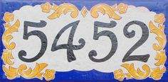 A beautiful 8x16 house number plaque. Choose another border color for this stunning house number plaque. It is hand painted and kiln fired on an off white/light grey tile. Your house numbers (or any text) will be hand painted in black 4 high numbers. The width of the numbers will be adjusted according to the amount of numbers. Add your family name, house name, etc. in the area below the numbers. Name will measure approx. 1.5 x 5 . If no name is chosen then no problem leaving it empty.  T...