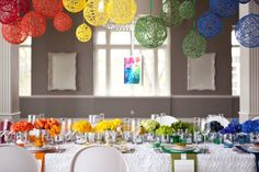 A rainbow theme tabletop with centerpieces. Each place setting matched the floral facing each guest.