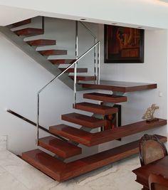 Scala contemporanea in rovere con una trave metallica al centro dei gradini. Il primo e il terzo piano si trasformano in mensole