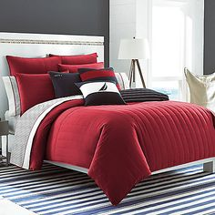 The Mainsail comforter set features classic Nautica red solids accented with sporty quilting and logo label detailing. This versatile bed reverses to a tailored shirting stripe in navy and ivory finished by contrast double-needle stitching.