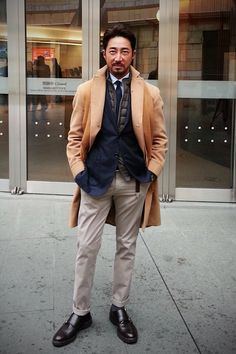 Layers:  mustard scarf over tan coat over navy blazer over grey puffy vest over white shirt w/ navy tie, grey pants, black shoes