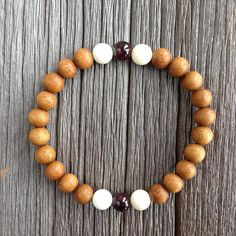 Mens beaded wood bracelet in Madre de Caco accented with Coral and Garnet. Features: ~ 8mm madre de cacao wood beads ~ 8mm white coral beads (x4) ~ 8mm garnet beads (x2) ~ Strong, non-fraying elastic cord; simply slide bracelet on and off wrist ~ Flat rate shipping for all orders