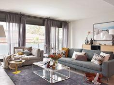 Un salón en tonos grises con grandes ventanales
