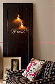 De uma porta sem uso no apartamento, Marcio Mota fez um quadro de avisos na sala. Depois de pintá-la com tinta de lousa, ele pendurou os fios com as duas lâmpadas douradas espelhadas, da Lustres Yamamura