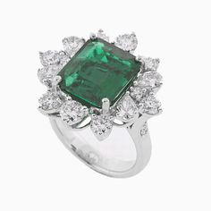 Set in platinum is an exquisite emerald center stone of immense size and color. Weighing a colossal 5.77ct, it is surrounded by a wreath of the finest premium cut rounds diamonds totaling 1.88ct