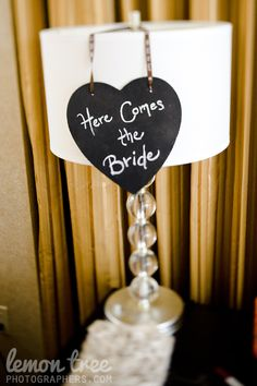 Wedding ceremony chalk boards that announce the bride coming down the aisle, held by the ring bearer.