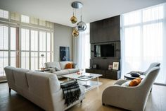 Trend Copper and Mixed Metals.  I really love the modern look to this room.  The clean lines throughout the windows, the huge cement block of wall as the center focal point.   The pops of orange, and of course the three gold and sliver lighting fixtures hanging from the ceiling.  Overall this room is airy, simple, clean, and very modern.  I love it!