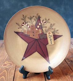 """Believe Star Plate with Gingerbread, by The Hearthside Collection. This primitive plate features painted pine sprigs, candy canes, and a gingerbread man tucked into a burgundy star against a tan background. Tag reads: """"Believe."""" Measures approx 12 inches. Made of hand-painted pressed wood, antiqued and distressed for an aged, rustic look. Decorative use only (not foo..."""