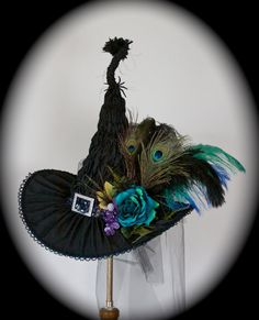 Such a beautiful hat in shades of peacock blues and greens!  The topside of this hat is spectacularly ruched in black matte material with a striking