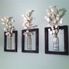 Homemade picture frames..Just take a frame w/out the glass or backs on them and hang them,then put a glass bottle (preferably flat) in the middle of the frame and then add flowers of your choice in bottle.