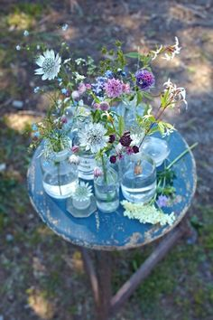 Lovely and simple centrepieces for your table - old jam jars and glass bottles with spring flowers from the garden #spring #home #flowers #recycle