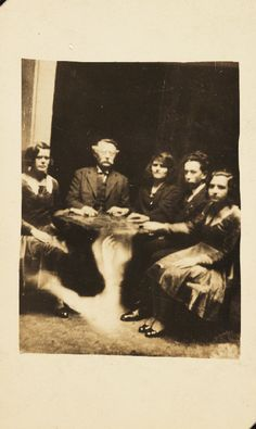 "Photo of a group at a seance, c 1920 by William Hope, ""spirit photographer""  The information accompanying the spirit album states that the table is levitating - in reality the image of a ghostly arm has been superimposed over the table.  Hope's ""Spirit Photography"" work gained momentum after WWI, when many people were desperate to find evidence of loved ones living beyond the grave.  His techniques used double and triple exposures to render the appearance of ghostly apparitions."