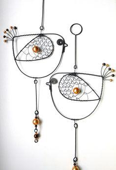 Ptáček Hnědáček Ptáček je vyroben z černého drátu a dozdoben perleťovými korálky.Velikost patáčka je cca 10x27cm. Ptáček slouží jako dekorace.Drátek je ošetřen proti korozi. Cena za kus.