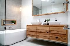 Modern bathroom design featuring timber vanity, shaving cabinet and nook.  Wall tiles white and grey.  Timber pieces by Bombora custom furniture