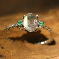 Oval labradorite ring with faceted emerald side set gems in prongs setting with sterling silver oxidized twist design band