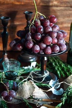 Grapes as table centres mixed with silver plates, foliage and ivy