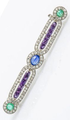 An early Art Deco 18k white gold, diamond and gem-set bar brooch, Michel Ballada, French, circa 1910. The interlaced lines set with rose-cut diamonds centring a sapphire cabochon, with a line of calibré amethysts on either side, and set with two emerald cabochons on each terminal. With maker's mark MB.